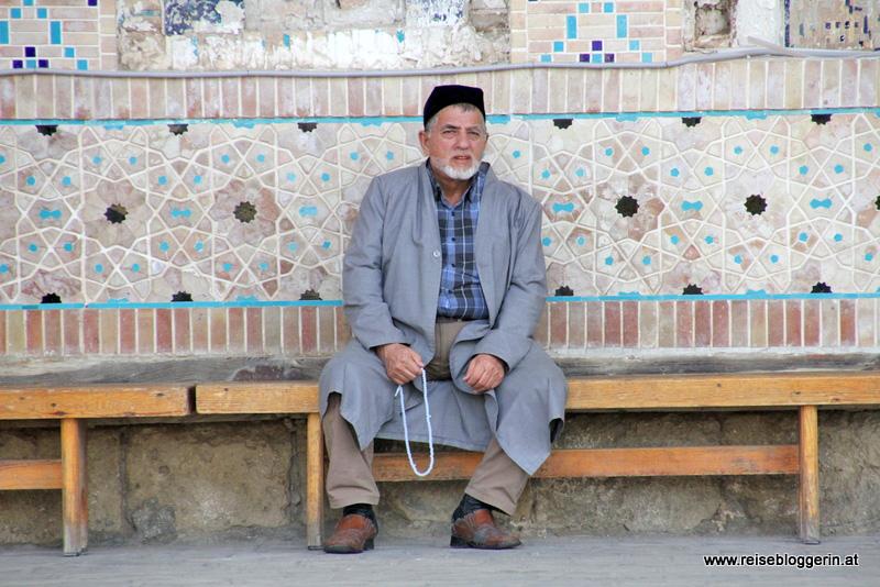 Ein Usbeke sitzt vor der Moschee