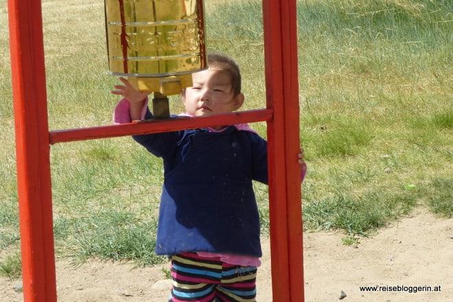 Mongolisches Mädchen mit einer Gebetsmühle