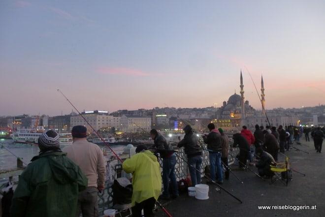 Fischer stehen Schulter an Schulter auf der Galatabrücke, im Hintergrund sieht man eine Moschee