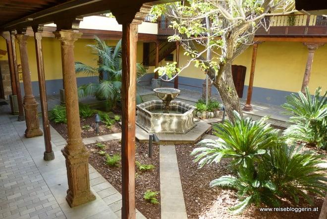 Ein Innenhof mit Pflanzen und einem Brunnen