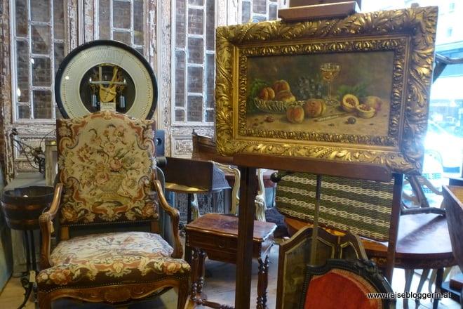 Ein alter Lehnstuhl, ein Bild mit Pfirsichen und eine alte Personenwaage in einem Trödlerladen