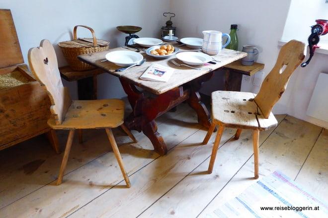 Ein alter Holztisch mit zwei Stühlen