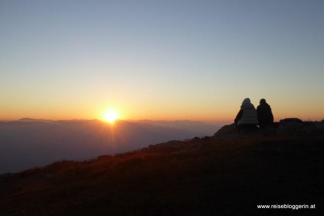 Zwei Personen warten auf die Sonne bei der Sonnenaufgangsfahrt Goldeck