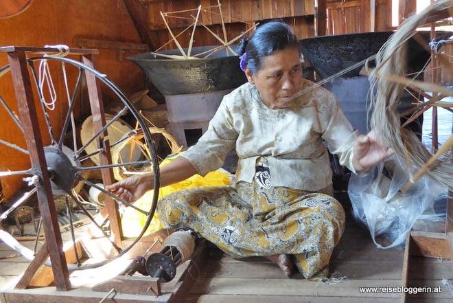 Lotusseide wird am Spinnrad weiterverarbeitet