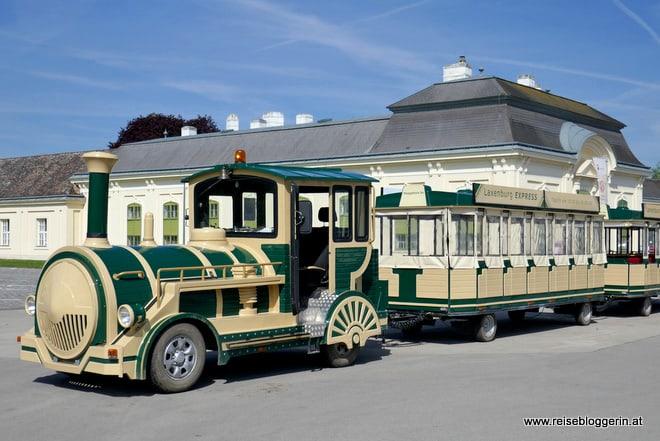 Der grün-beige gestrichene Bummelzug fährt durch den Schlosspark Laxenburg