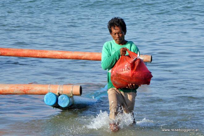 Ein Fischer bringt seinen Fang an den Strand von Jimbaran