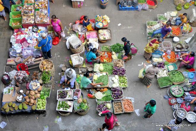 Der Markt in Ubud - Verkäuferinnen sitzen über grünen Bohnen, Tomaten und anderem Gemüse