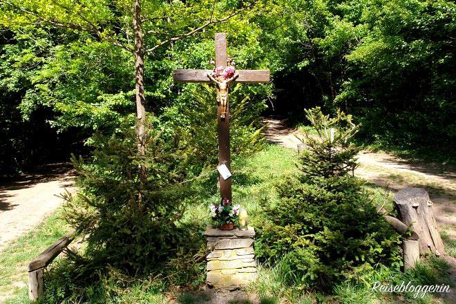 Ein Kreuz aus Holz an einer Wegkreuzung