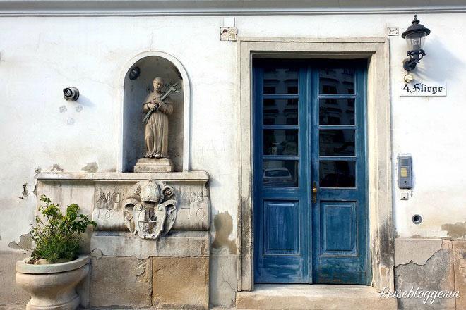 Eine blaue abgeschabte Tür mit einer Laterne, an der Wand steht eine Heiligenfigur