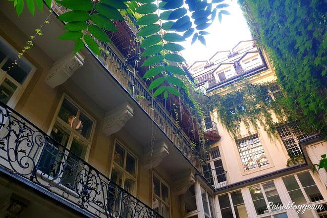 Der Innenhof vom Nestroy Geburtshaus. Efeuranken winden sich über schmiedeisene Balkone.