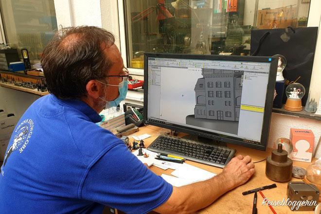 Der Seniorchef macht einen Entwurf am Computer für eine Schneekugel