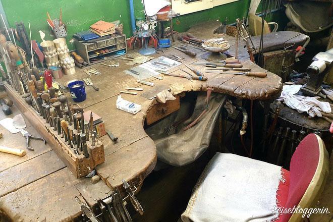 Eine Werkzeugbank aus Holz mit Werkzeugen in der Silberwerkstatt Vaugoin