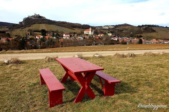 rote Picknickbänke mit Aussicht auf die Burg