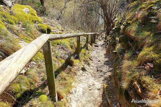schmaler Wanderweg mit Geländer aus Holz