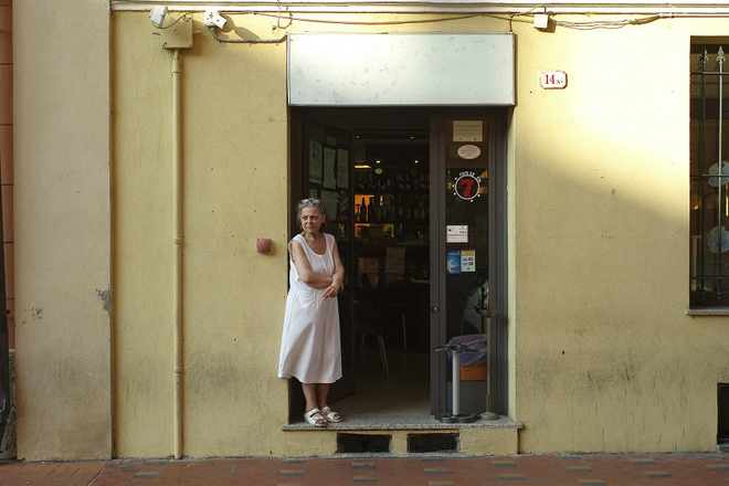 Alte Frau steht in einer Tür