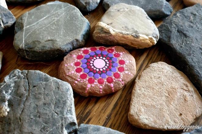 bunt bemalter Stein inmitten anderer Steine